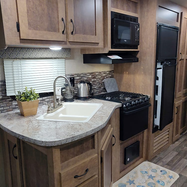 Kitchen with a double bowl sink, gas range with 3 burners, oven, microwave and refrigerator