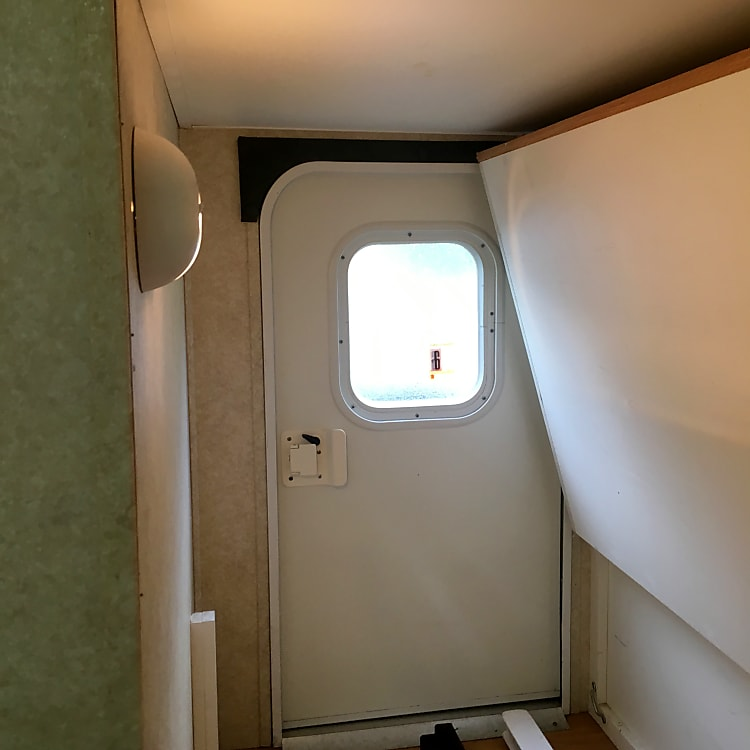 "Interior view showing ""bicycle door,"" which allows access to lower bunk and storage area."