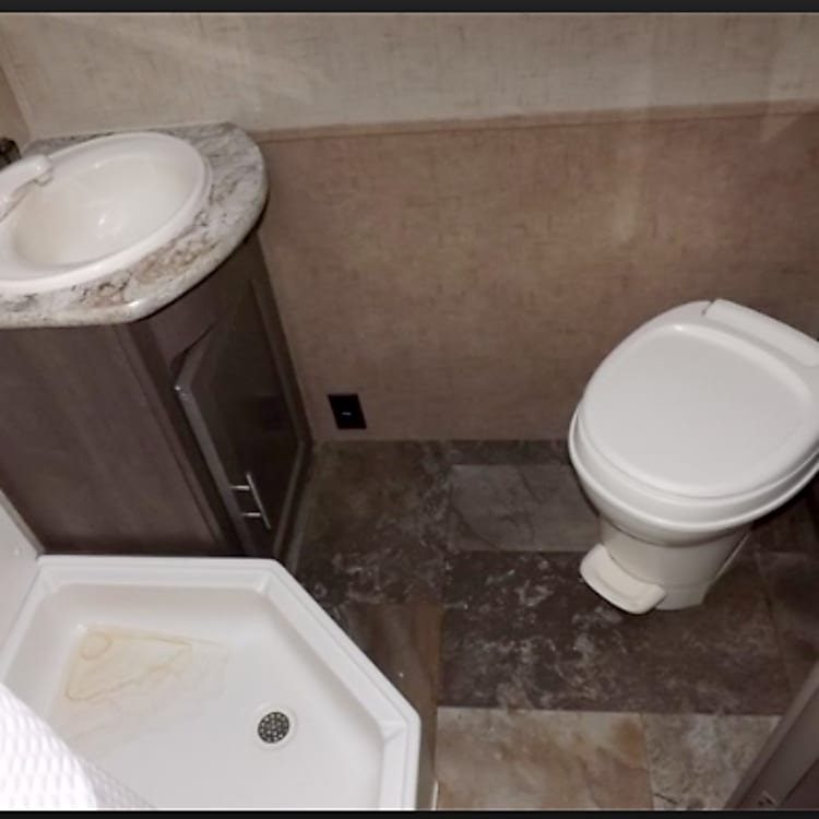 Another view of bathroom...also has a closed shelving behind toilet