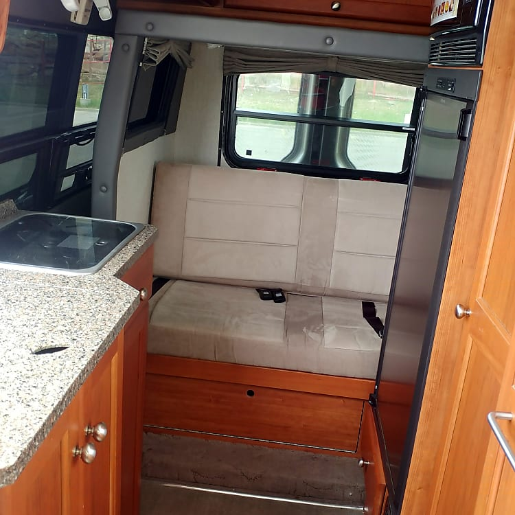 View to Rear with Slide Retracted Ready for Driving - Sink (with cover in place), 2 Burner Stove on Left; Rear Seating for 2 Persons; on Right Fridge Door and Storage Closet.