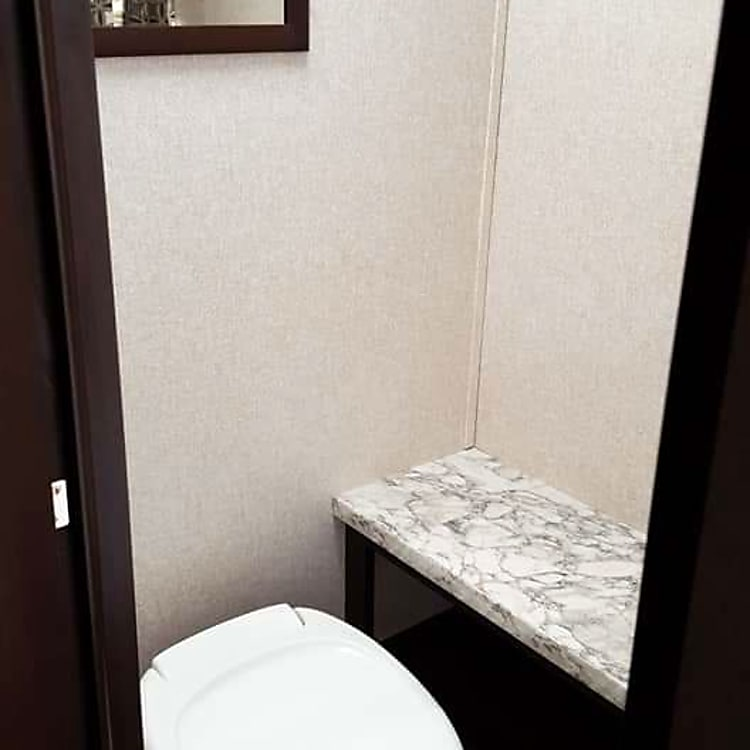 Bathroom with toilet, storage, towel bars, and shower.