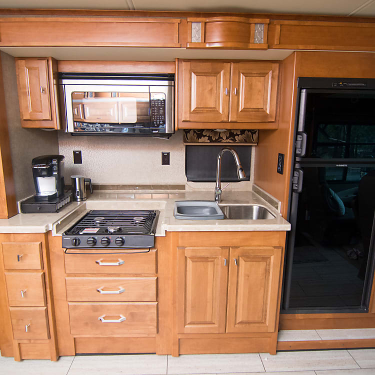 Kitchen with stove top, microwave oven, sink and refrigerator. Can optionally be rented with table setting for 8, stemless wine glasses, Keurig coffee pot, cookware and serveware.