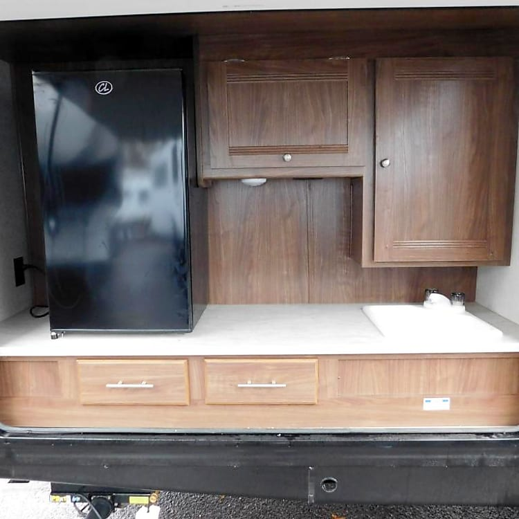 Outpost kitchen. Fridge and TV Jack with sink and cabinet. Also features attached gas grill.
