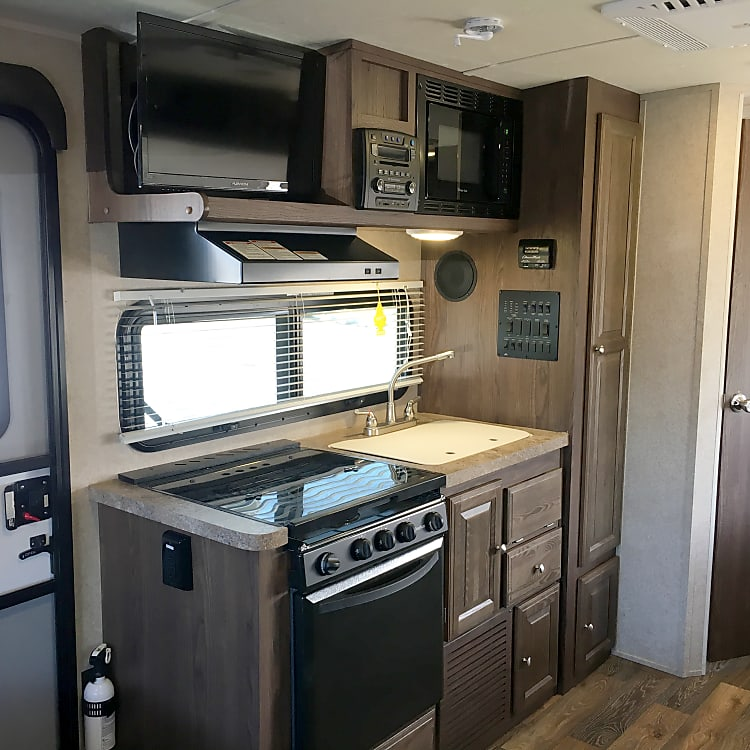 So much convenience when you're out on your adventure: double bowl sink, 3 burner gas stove, gas oven, venting hood, microwave!