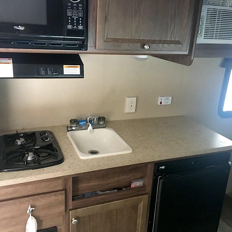 Stove, microwave, sink, fridge, and ac unit.