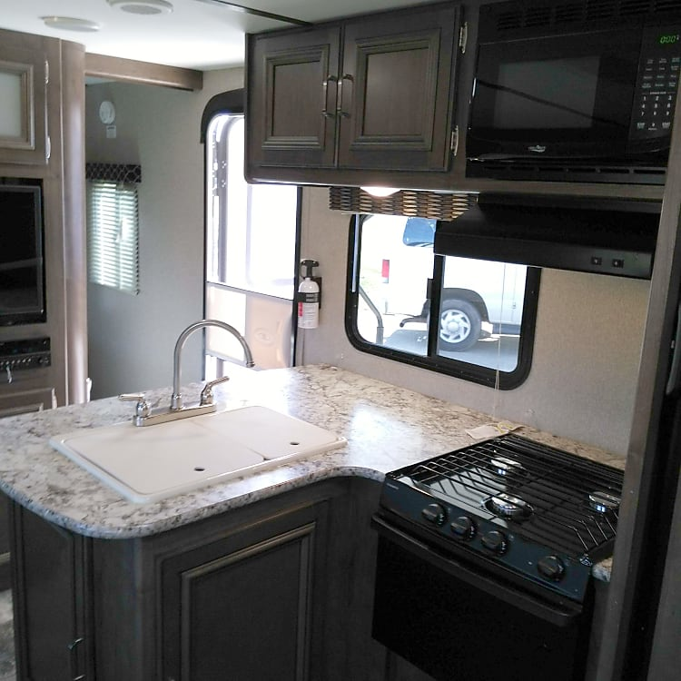 Double sink.  Gas stove, oven, and microwave.  Toaster oven and coffee maker included.  Refrigerator with freezer.