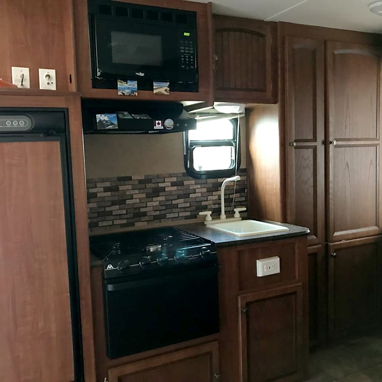 Kitchen area with stove, microwave, oven, sink and fridge.