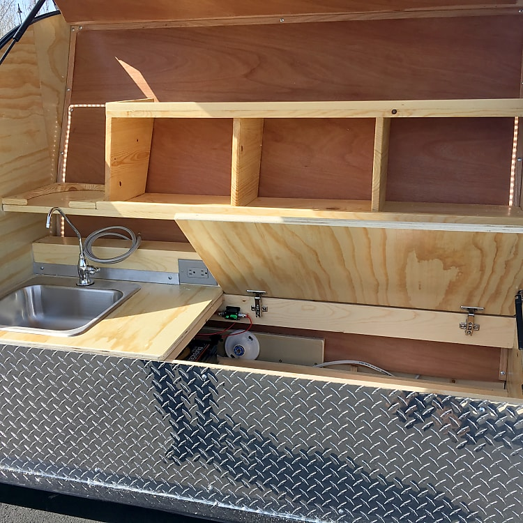 Galley kitchen has plenty of storage and a gravity powered faucet
