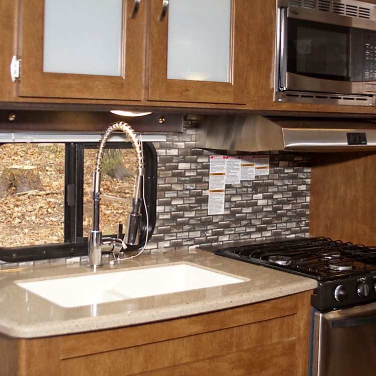 There is a microwave, 3 burner cooktop with light & fan above, small oven, sink with spray faucet option, nice sized cabinet above, cabinet below the sink and 2 drawers.