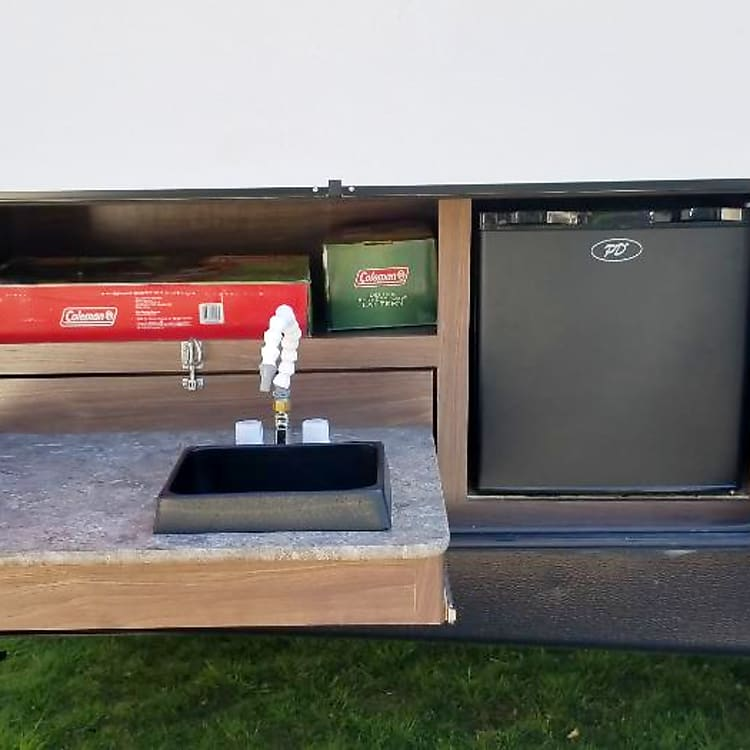 Outdoor kitchen with hot/cold water, mini fridge, and coleman stovetop.