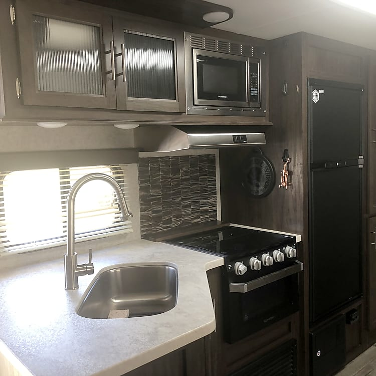 Kitchen.  Large sink with drying rack.  Microwave, refrigerator and freezer, Keurig included in kitchen.  Silverware set, plates, bowls, pot/pan also included.