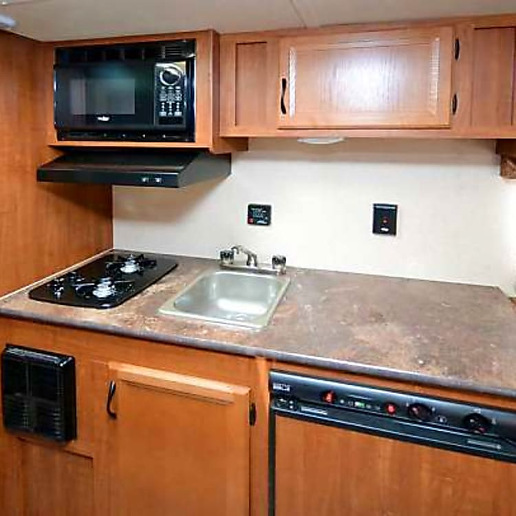 Nicely appointed kitchen with sink, two-burner stove, microwave, refrigerator, and plenty of cabinets for food and sundries.