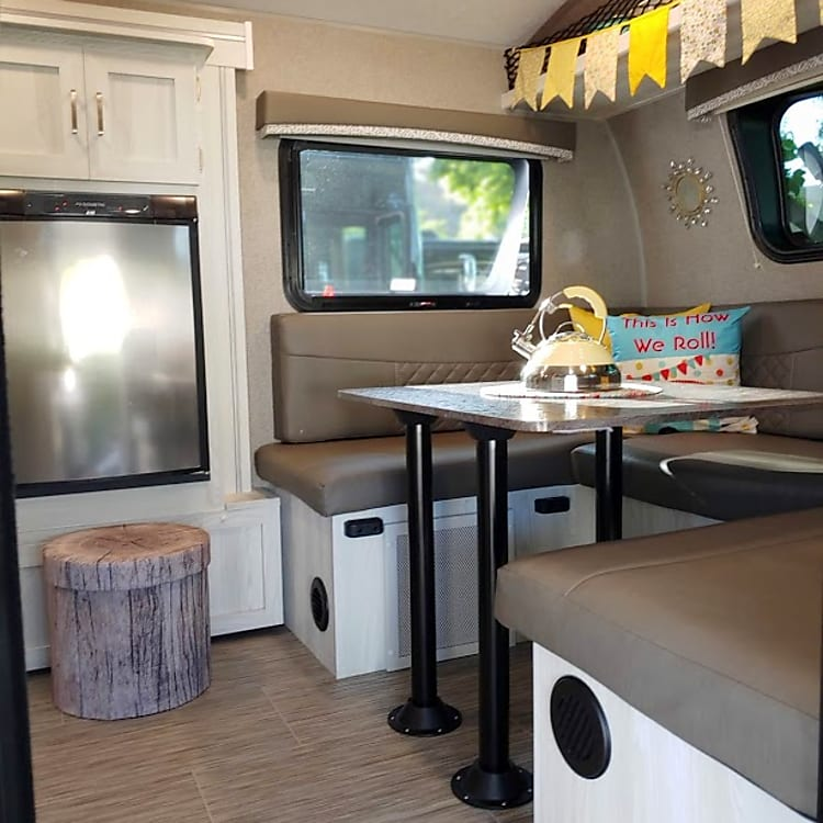 The entry into the dinette has a nice size refrigerator with a cute faux wood storage which holds the kitchen linens.