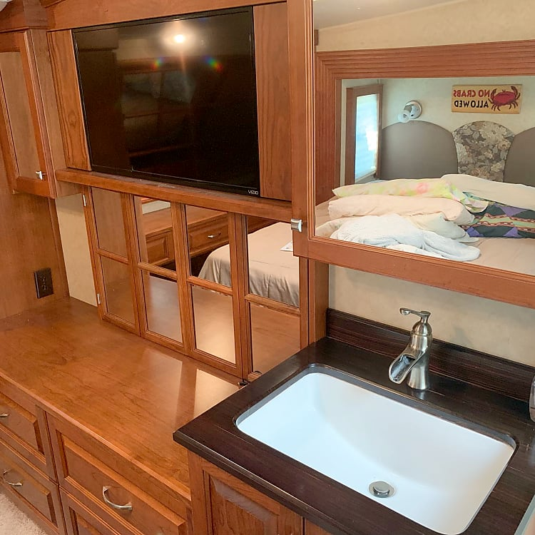Bathroom sink and dresser in master bedroom and flat screen