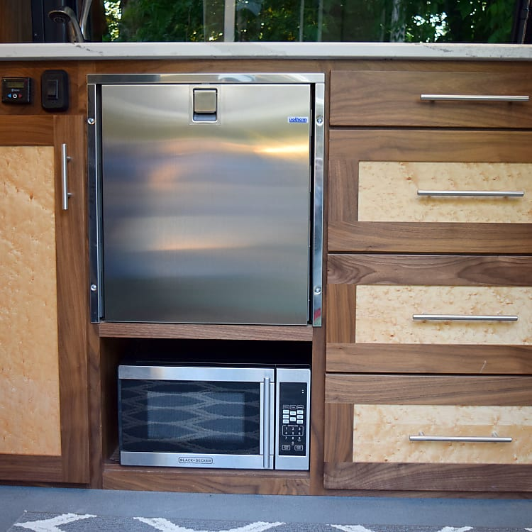 Cabinet in kitchen with fridge, microwave, drawers and control center