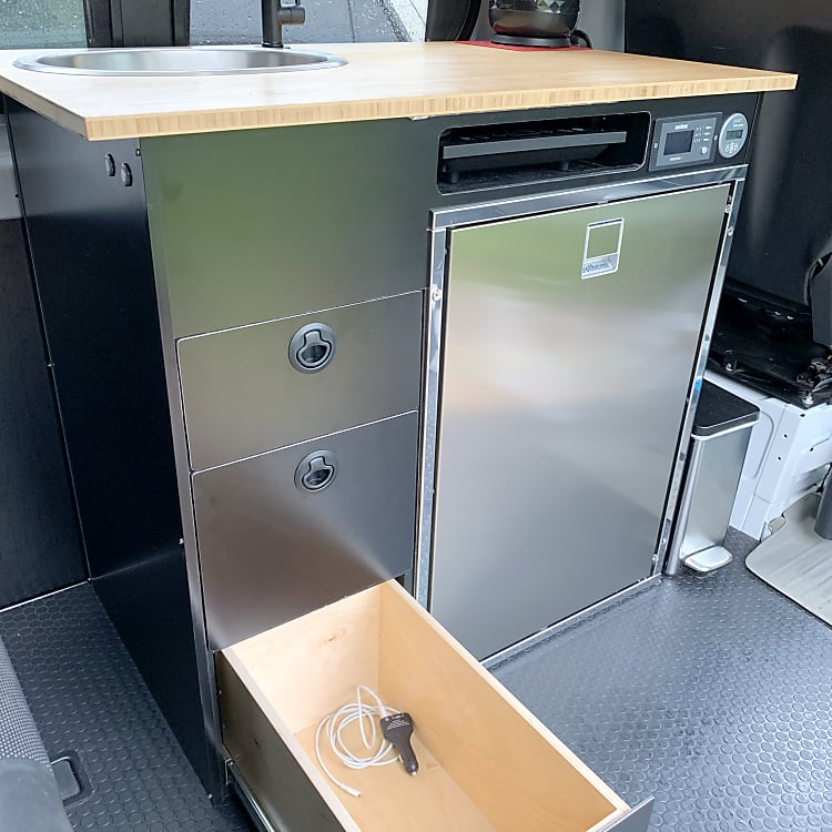 Three drawers for kitchen items and food storage.