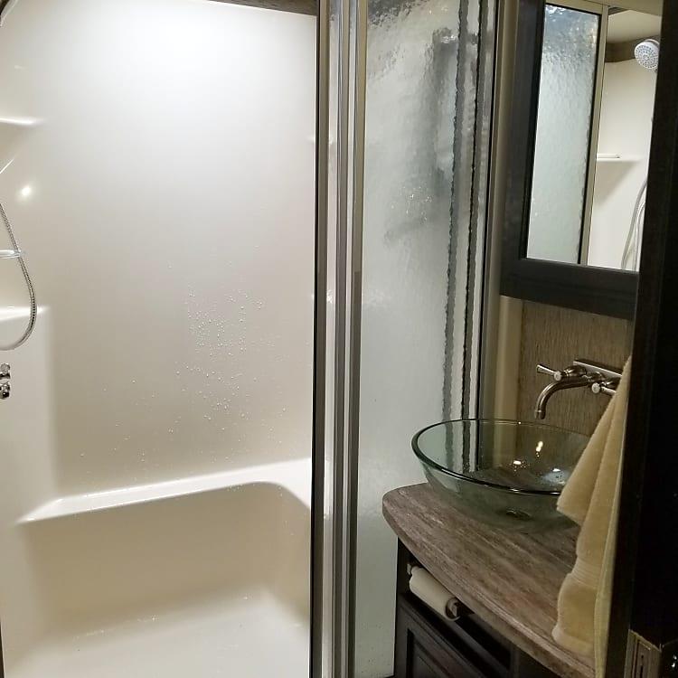 Main bathroom, medicine cabinet and cabinet storage.