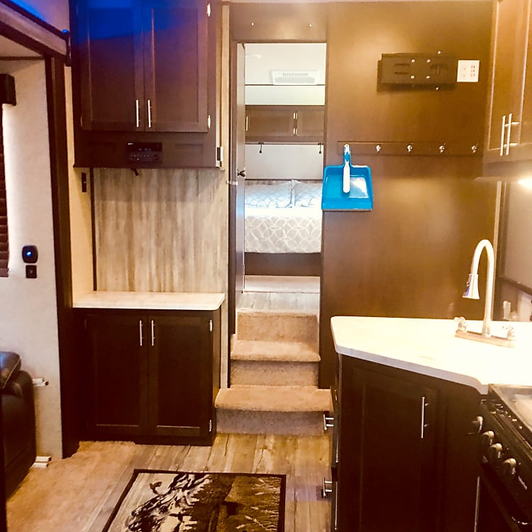 Additional upper and lower cabinets in living area. Under upper cabinet there is a radio/CD/DVD component with Bluetooth. TV rack suspended above hooks for optimal viewing of television while sitting on couch or up in loft.