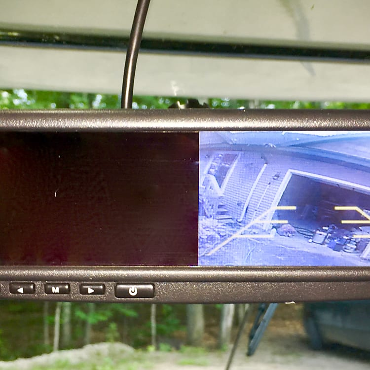 Back up camera located in rear view mirror which activates when transmission is placed in reverse