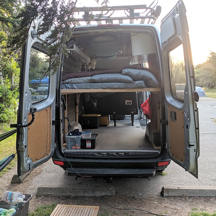 Rear view of the van showing the platform bed and space underneath for all your adventure gear!