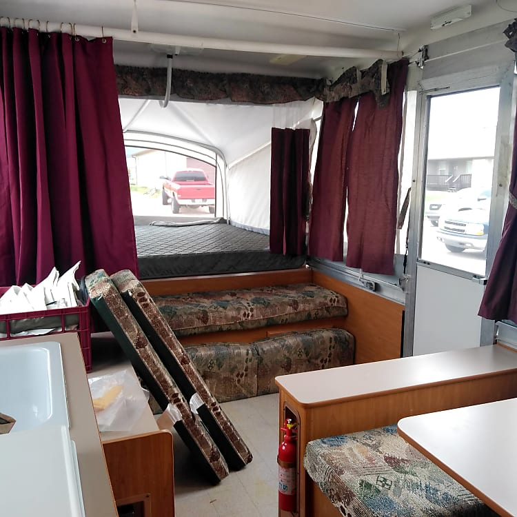 """This is the view of the """"front end"""" of the camper.  We've got a King bed and a couch that folds out into a twin on this end! We've also got storage, Fridge and hot water heater over there too!"""