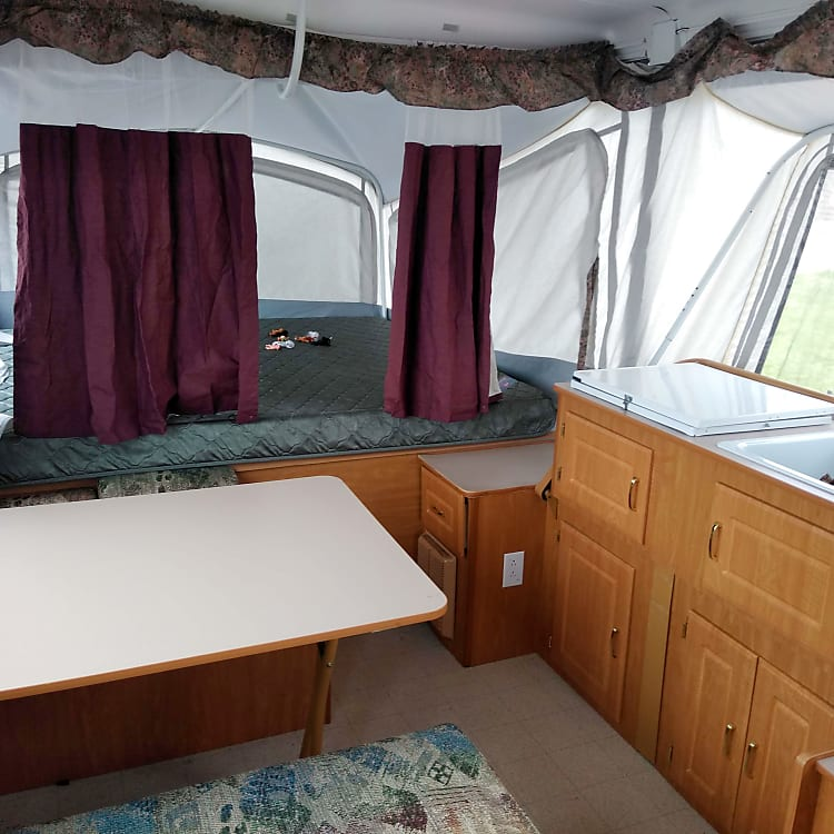 """this is the """"back end"""" of the trailer.  we've got ANOTHER king sized bed  the table folds down into a FULL  on this end is out pop out kitchen galley with fully working sink (with HOT WATER) and stove!"""