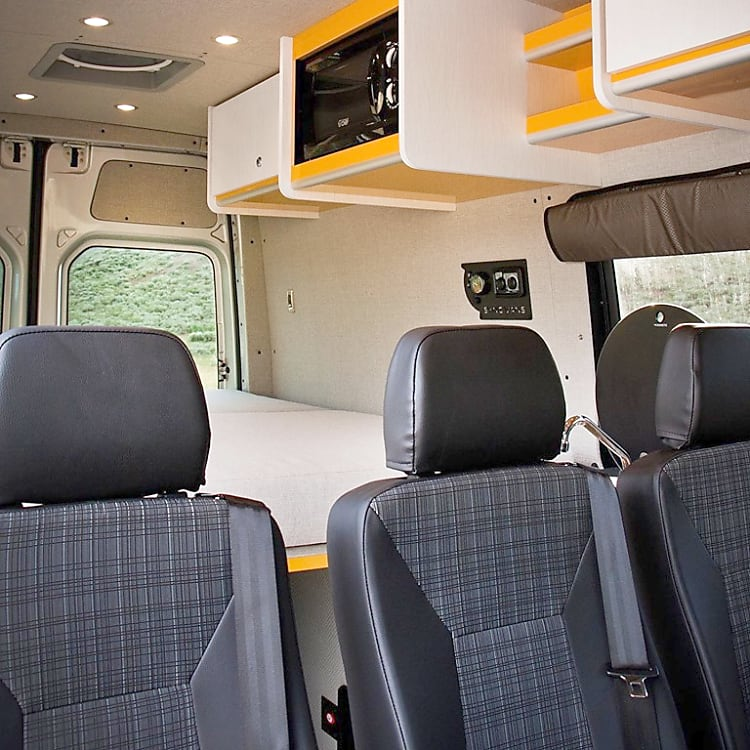 Three removeable jump seats (one with carseat latch anchors) allow for maximum versatility.  Overhead built-ins include two large storage cabinets, two shelves, and a microwave.  The queen mattress comfortably sleeps two adults but can be folded up for additional space or removed altogether.