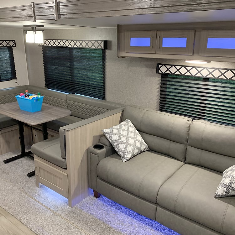 Living room area with a large sleeper sofa and U-shaped dinette.