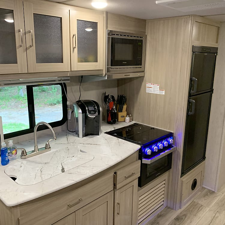 Kitchen with 3 burner gas oven/stove. Coffee maker, kitchen knives and basic utensils.