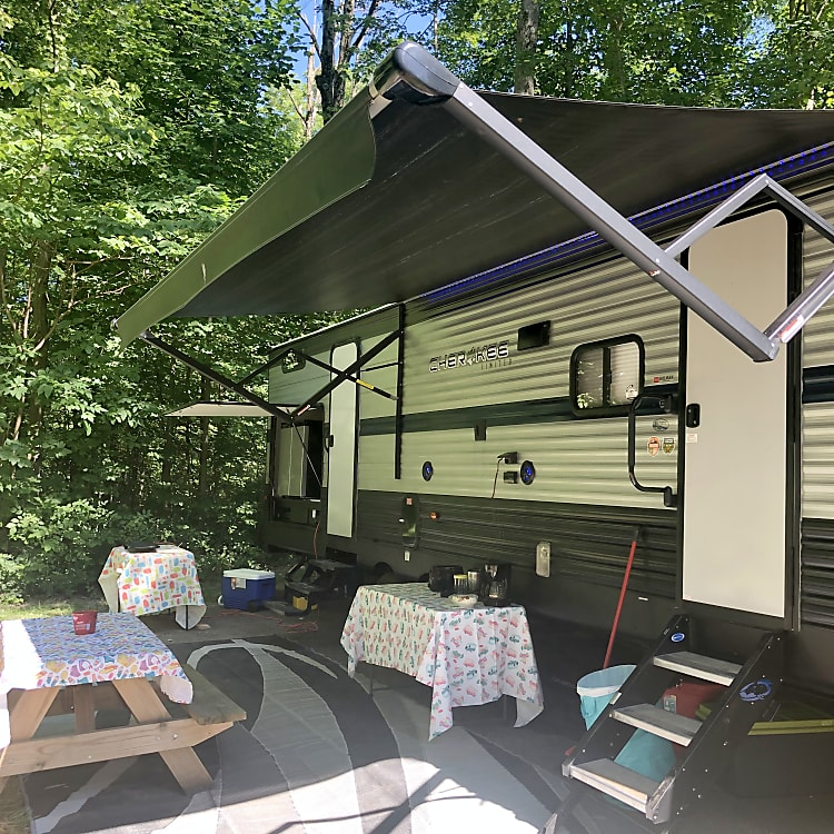 Camper includes 2 fold up tables and 1 picnic table with benches and many table clothes
