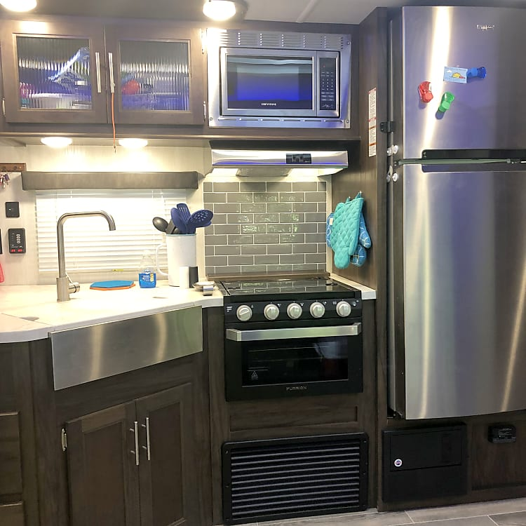 Interior Kitchen features Stainless Steel appliances,  3 Burners stove and oven.  Hot and Cold water and microwave.  Pots and pans and cooking utensils included