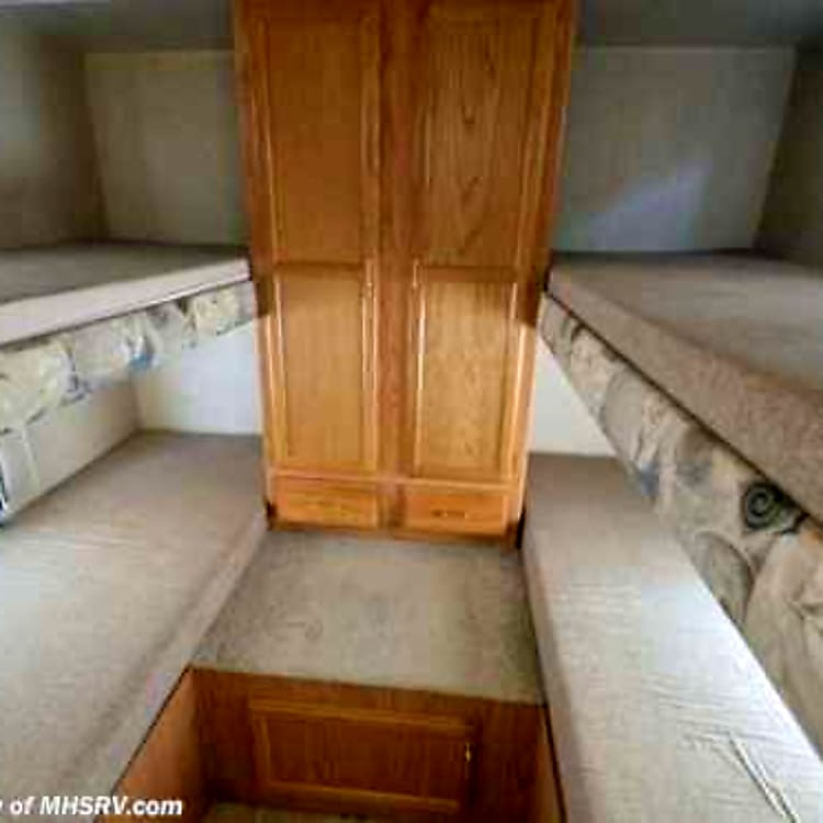 4 single bunk beds (quad bunks) in back with wardrobe closet and two drawers.