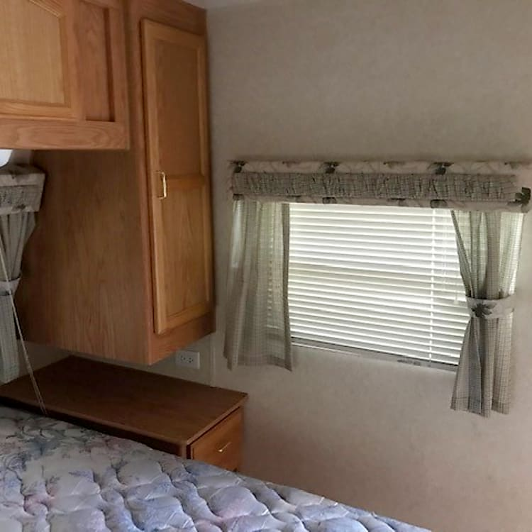 Master bedroom, window at front and each side. Bed surrounded by wardrobe closets, two upper cabinets, side tables with drawers. Bed lifts up for additional storage.
