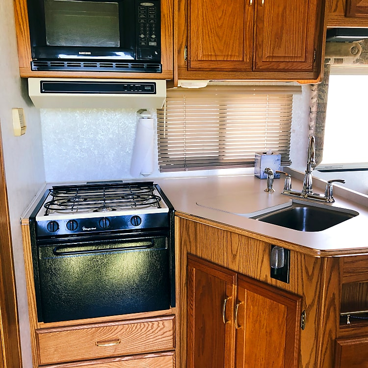 With this three burner stove and oven you can make a large meal even if you're not grilling outside. Microwave is above the stove.