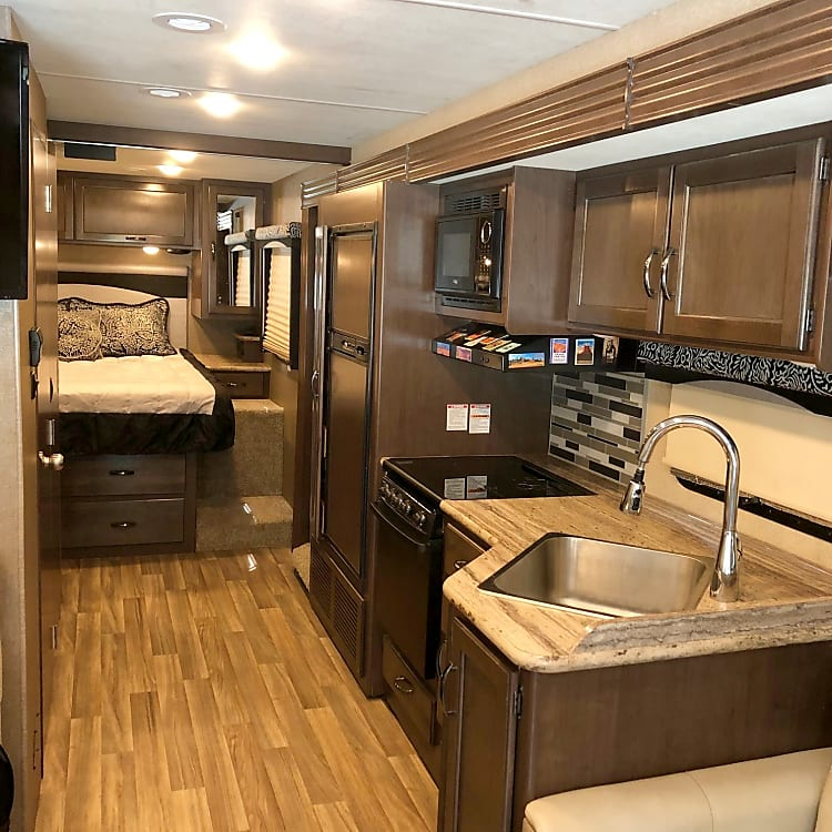 Interior view of coach with wall slide out. Comfortably spacious, similar to a small apartment - that you can drive! This view shows kitchen including refrigerator and microwave, plenty of storage/cabinet space, and the master bedroom at the rear of the coach.