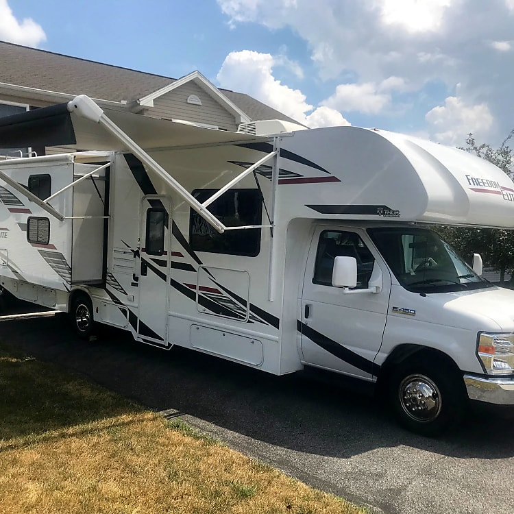 Thor 30' Freedom Elite features an electric awning and one slide out on the passenger side. LED lights under the awning provide illumination when it's campfire time. External TV is located behind passenger side cab.