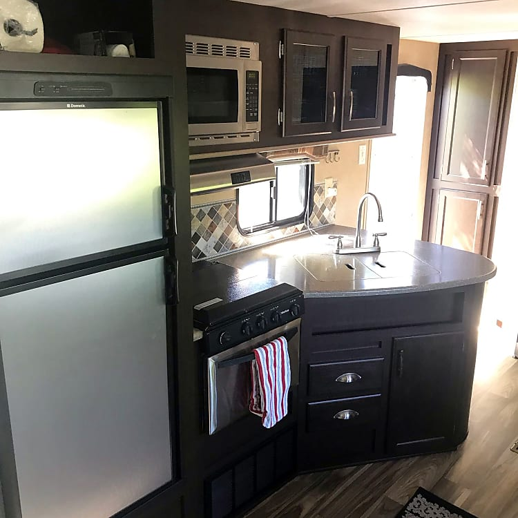 Kitchen - complete with fridge, freezer, microwave, oven, range, cooking tools, and serve ware.