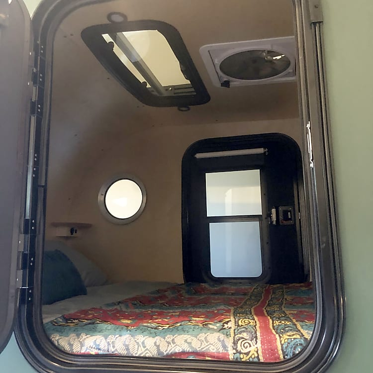 Inside the cabin you will see the following: moonroof, fan, side tables with USB ports, fan with multiple speeds, dimming lights, and doors on both sides with blackout shades. As you can see, there is a spacious queen bed complete with linens so you can load your items and hit the road! Not pictured: storage inside of cabin.