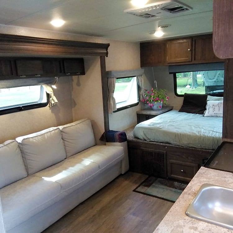 Beautiful view. Of SLIDEOUT ! YES THIS GORGEOUS CAMPER HAS A SLIDE OUT... !😋😋😋 Couch is extremely comfortable Plenty of Overhead cabinet storage Even behind the couch