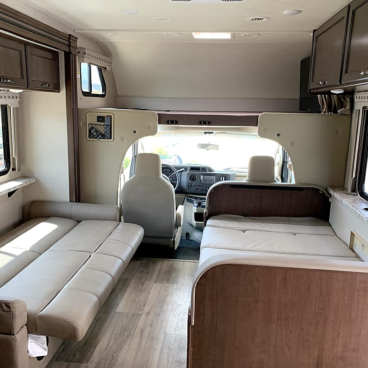 Interior front sleeping options.  Large queen size bed above the cab along with couch and dining table that turn into beds.