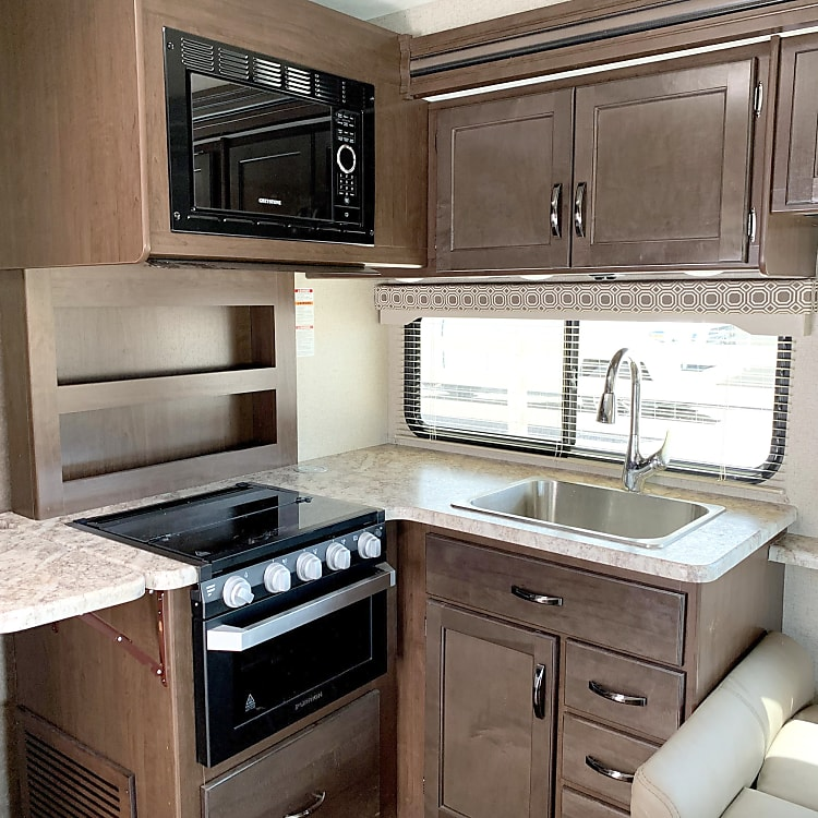 Kitchen is comprised of a microwave, 3-burner stove, an oven, and a large sink.