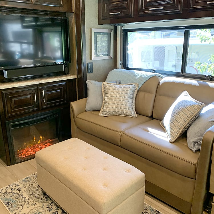"""Within the living area, you will find extra storage under the sofa, electric fireplace, 40"""" flat-screen TV with Always-in-View Slide System, Blu-ray player and Bluetooth sound bar.  Storage ottoman to help you relax can be included or removed before your rental, based on your preference/needs."""