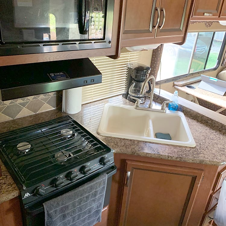 The kitchen features a stove top, oven, microwave, and coffee maker. Just like home while enjoying nature just steps away!
