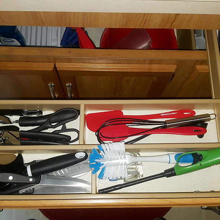 Cooking Utensils. Down below the sink is mixing bowls and cut board. Along with some cooking pans!