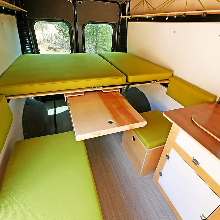 Inside there is a bed for two that adjusts to a lounger, a slide-away table with two seats, and a kitchen with stove, sink and Dometic 12v refrigerator. All cooking implements and bedding included. There is a chemical toilet.