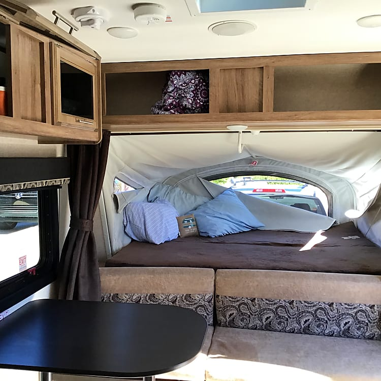 Bed at the front of the camper, door would be on the right side of photo and kitchen table to the left.