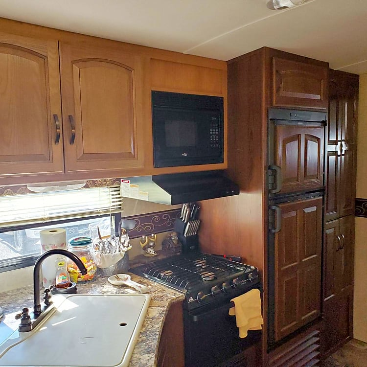 Kitchen with gas oven and cooktop + microwave, and large sink and fridge/freezer
