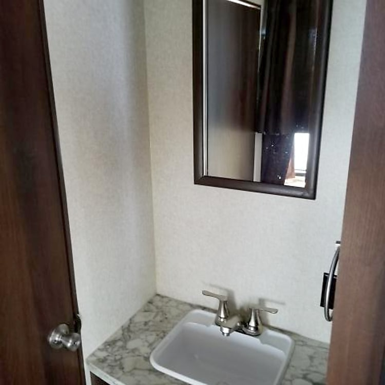 The bathroom sink and mirror can be used while another is showering.