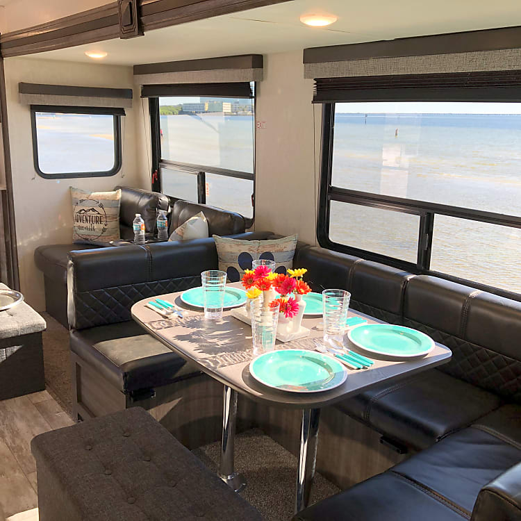 Full dinette with service for 8 plus the ottomans provide additional storage, seating or footrests!
