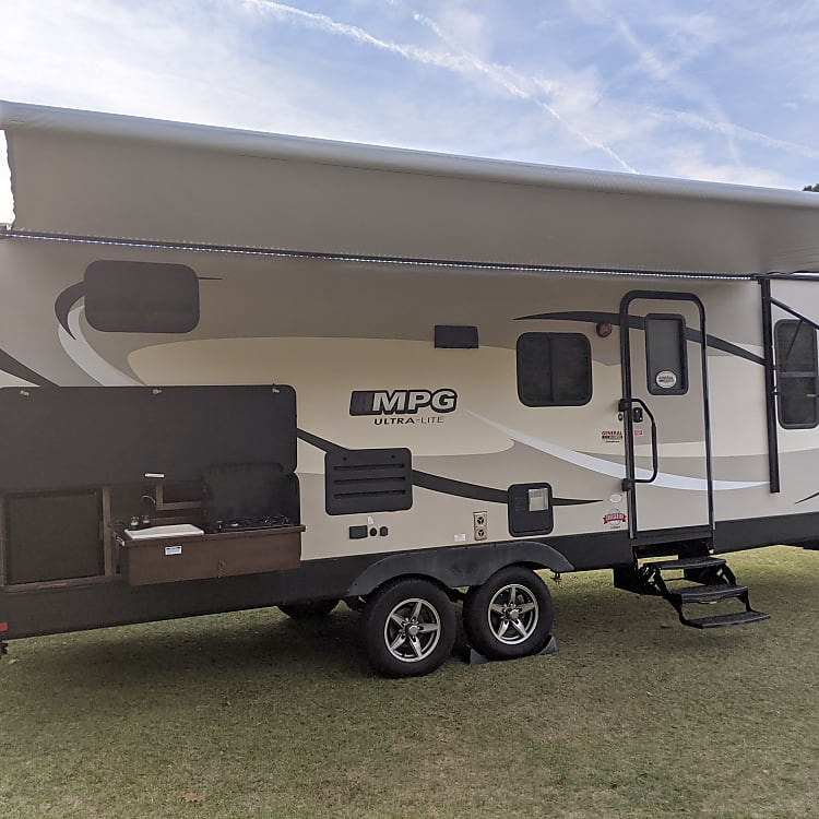 Exterior camper with large awning and outdoor kitchen.  Entry door has screen door for bringing the outdoors in.